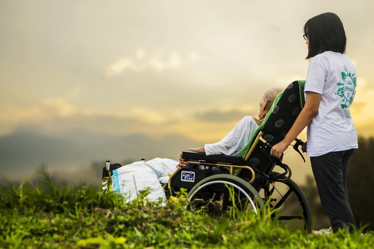 車椅子に乗った老人と介護者