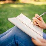 座りながらノートを書く人