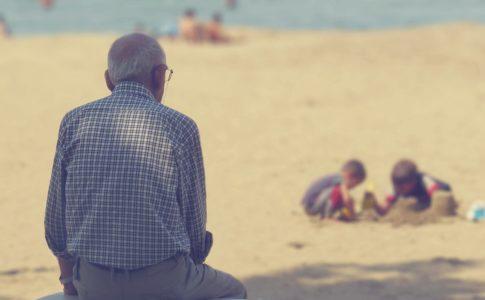 砂場で遊ぶ子供を見守る老人